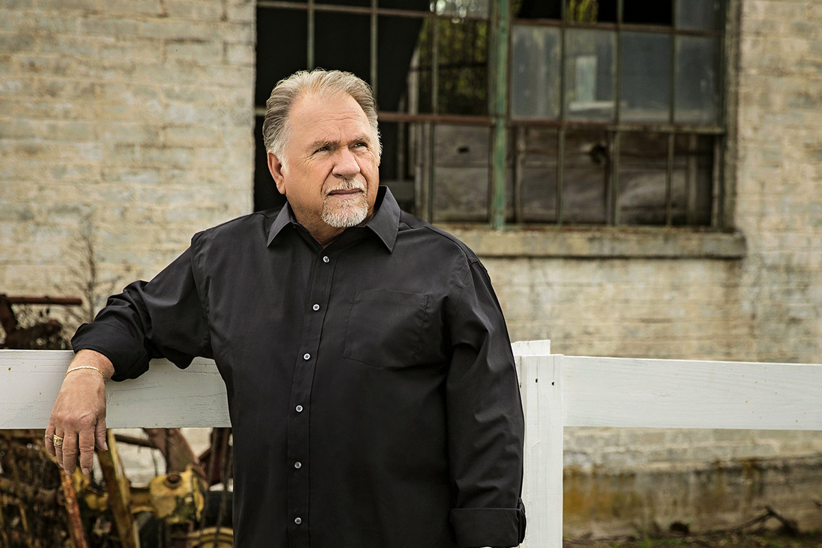 Gene Watson standing next to a fence