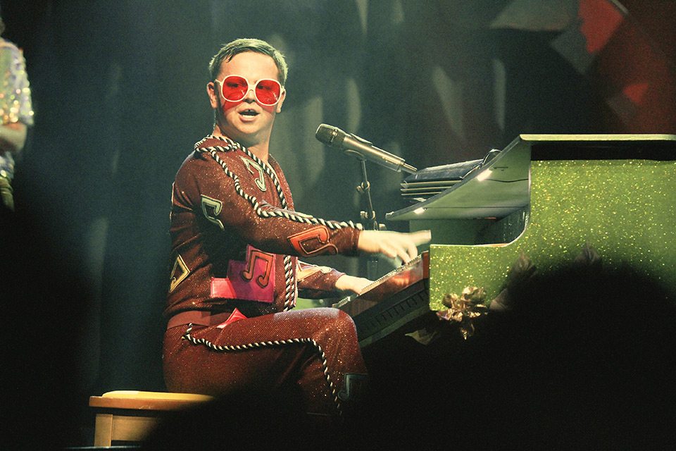 Rus Anderson as Elton John playing a piano