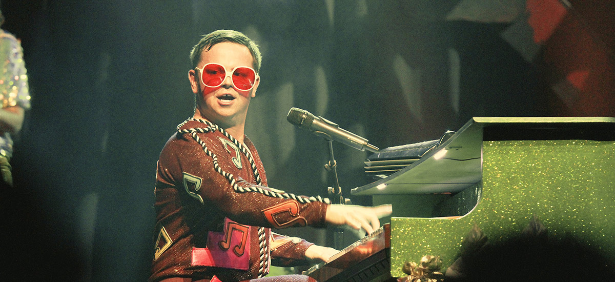 Rus Anderson as Elton John playing the piano during a performance